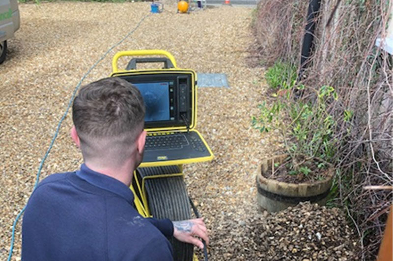 Drainage engineer carrying out a CCTV survey using a camera unit and drain camera
